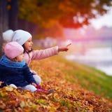 Deux belles filles s'asseyant en parc d'automne Photo stock