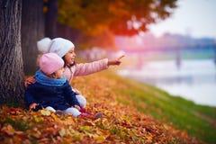 Deux belles filles s'asseyant en parc d'automne Photo libre de droits