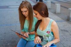 Deux belles filles s'asseyant sur un banc avec le PC de comprimé Photo stock