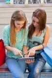 Deux belles filles s'asseyant sur un banc avec le PC de comprimé Photographie stock libre de droits