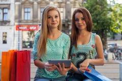 Deux belles filles s'asseyant sur un banc avec le PC de comprimé Photos stock
