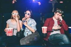 Deux belles filles s'asseyent ensemble La fille blonde mange du maïs éclaté tandis que son ami boit le coke Le type est Images libres de droits