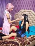Deux belles filles sur un lit, regard sensuel à l'un l'autre Photo libre de droits