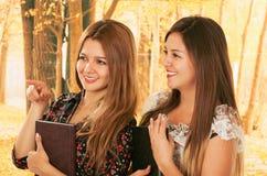 Deux belles jeunes étudiantes au-dessus de la chute Images libres de droits