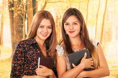 Deux belles jeunes étudiantes au-dessus de la chute Photos libres de droits
