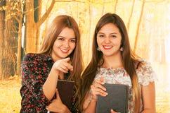 Deux belles jeunes étudiantes au-dessus de la chute Photos stock