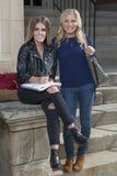 Deux belles jeunes étudiantes ensemble sur le campus Image libre de droits