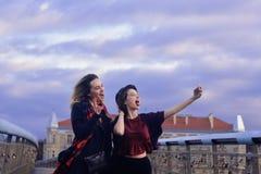 Deux belles jeunes amies d'étudiant ayant l'amusement faisant les visages drôles et prenant des autoportraits avec le Smart-télép Images stock
