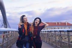 Deux belles jeunes amies d'étudiant ayant l'amusement faisant les visages drôles et prenant des autoportraits avec le Smart-télép Photos libres de droits