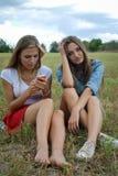 Deux belles jeunes dames s'asseyant ensemble dessus Images stock