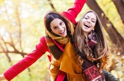 Deux belles jeunes femmes appréciant en parc Image stock