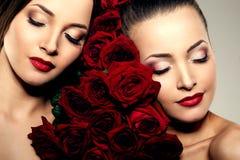 Deux belles jeunes femmes avec le maquillage étonnant dans les roses Cosmeti Photo stock