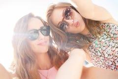 Deux belles jeunes femmes ayant l'amusement dans la ville Images stock