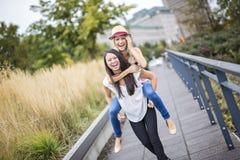 Deux belles jeunes femmes ayant l'amusement dans la ville Image stock