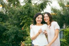 Deux belles jeunes femmes bien habillées causant dehors au-dessus de la Co Photos libres de droits
