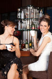 Deux belles jeunes femmes buvant du café au bar Images stock