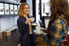 Deux belles jeunes femmes buvant du café et parlant dans un café Photos stock