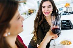 Deux belles jeunes femmes buvant du vin tout en mangeant Photographie stock