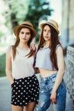 Deux belles jeunes femmes dans des chapeaux ayant l'amusement dans la ville Été chaud Filles dans des lunettes de soleil image libre de droits