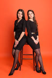 Deux belles jeunes femmes dans des costumes sur un fond rouge Photos stock