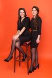 Deux belles jeunes femmes dans des costumes sur un fond rouge Photographie stock
