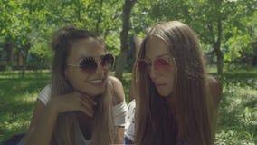 Deux belles jeunes femmes dans des lunettes de soleil sont mensonge sur l'herbe verte banque de vidéos