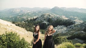 Deux belles jeunes femmes dans des robes noires snob posant ensemble sur l'appareil-photo dans la perspective d'un paysage de mon banque de vidéos