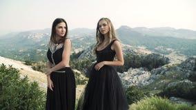 Deux belles jeunes femmes dans des robes noires snob posant ensemble sur l'appareil-photo dans la perspective d'un paysage de mon clips vidéos