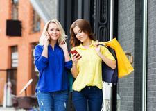 Deux belles jeunes femmes faisant des achats Image stock