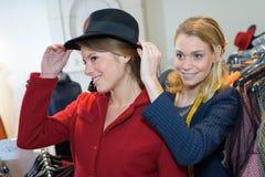 Deux belles jeunes femmes faisant des emplettes dans la boutique de vêtements Image stock