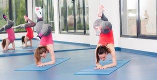 Deux belles jeunes femmes faisant l'exercice de gymnastique photo stock