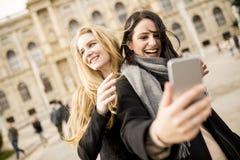 Deux belles jeunes femmes faisant le selfie dans la ville Image libre de droits