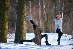 Deux belles jeunes femmes faisant le yoga dehors en parc d'hiver Images stock
