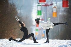 Deux belles jeunes femmes faisant le yoga dehors en parc d'hiver Photo stock