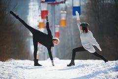 Deux belles jeunes femmes faisant le yoga dehors en parc d'hiver Image libre de droits