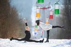Deux belles jeunes femmes faisant le yoga dehors en parc d'hiver Image stock