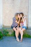 Deux belles jeunes femmes heureuses partageant le secret le jour d'été Image stock
