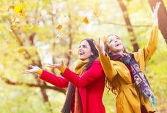 Deux belles jeunes femmes jetant des feuilles en parc Photos stock
