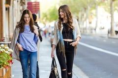 Deux belles jeunes femmes marchant et parlant dans la rue Photo stock