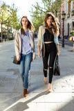 Deux belles jeunes femmes marchant et parlant dans la rue Photos stock