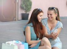 Deux belles jeunes femmes parlant après avoir fait des emplettes et se reposé dehors Photographie stock