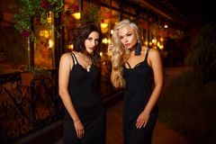 Deux belles jeunes femmes posant sur la caméra de lumières de la ville de nuit, de concept de beauté et de mode photo stock