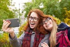 Deux belles jeunes femmes prenant des selfies tout en marchant dans l'Au Photos libres de droits
