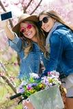 Deux belles jeunes femmes prenant un selfie dans le domaine Images stock