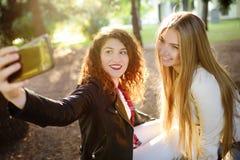 Deux belles jeunes femmes prennent le selfie sur le parc ensoleillé girlfriends image stock