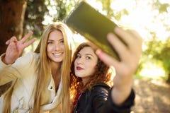 Deux belles jeunes femmes prennent le selfie sur le parc ensoleillé girlfriends photographie stock