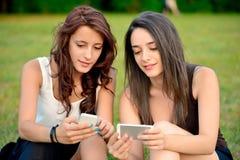 Deux belles jeunes femmes regardant les téléphones intelligents Photographie stock