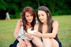 Deux belles jeunes femmes regardant les téléphones intelligents dehors Photographie stock