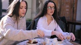 Deux belles jeunes femmes s'asseyant à la table dans le café ou le restaurant et ayant la femme de petit déjeuner versant un lait banque de vidéos