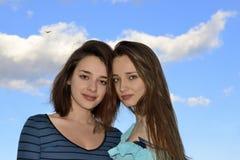 Deux belles jeunes femmes se tenant au-dessus du ciel bleu Photo stock